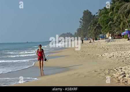 Rotes Kleid Frau geht barfuß in Wellen am frühen Morgen Lamai Strand Ko Samui Insel Thailand - Stockfoto