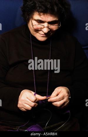 im Ruhestand Dame sitzt und strickt einen Schal - Stockfoto