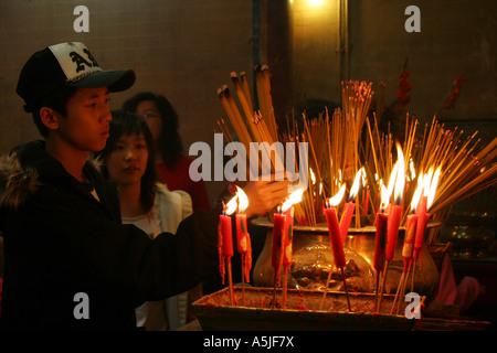 Chinesische Jugendliche in einem Tempel anzubeten - Stockfoto