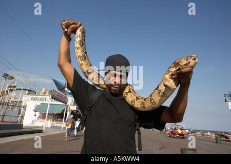Mann mit Haustier Python auf der Promenade in Coney Island