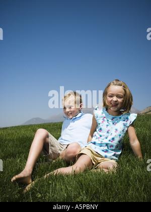 Jungen und Mädchen spielen auf einem Hügel - Stockfoto