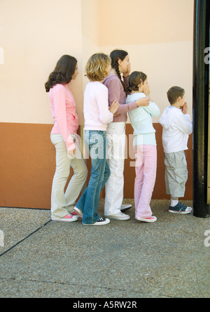 Gruppe von Kindern anstehen, Verkleidung Mund kommen Stockfoto