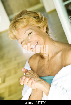 Ältere Frau Feuchtigkeitscreme auftragen - Stockfoto