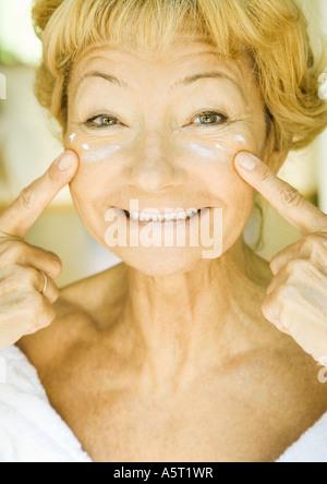 Ältere Frau Feuchtigkeitscreme unter den Augen auftragen - Stockfoto