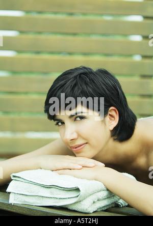 Frau mit Kopf auf Handtuch liegend - Stockfoto