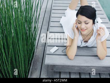 Frau liegend auf Liegestuhl Kopfhörer anhören - Stockfoto