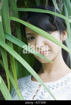 Frau stehend unter Blättern, Kopf und Schultern - Stockfoto