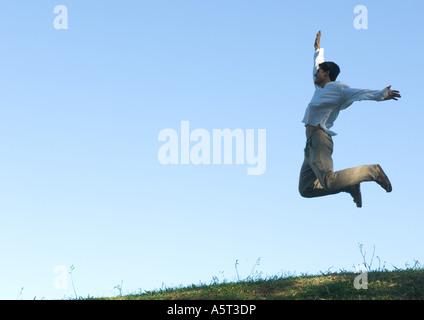 Mann, die Arme in die Luft springen - Stockfoto