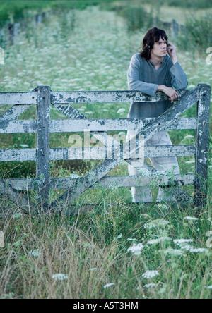 Man stützte sich auf Holzzaun, Kopfhörer anhören - Stockfoto