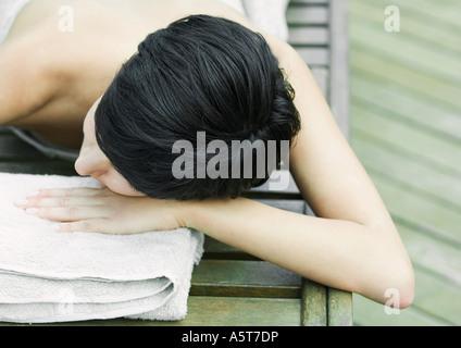 Frau liegend auf Bauch, eingewickelt in Tuch, Kopf auf Seite - Stockfoto