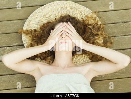 Frau liegt auf dem Deck, eingehüllt in Handtuch, Kopf auf die Matte, übergibt Augen - Stockfoto