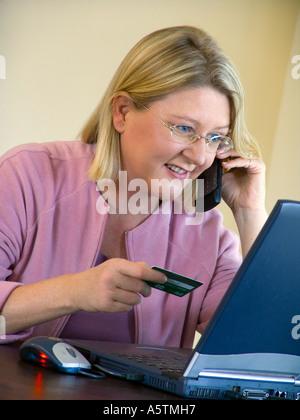 Laptop Debitkarte 30-35 Jahre selbstbewusste Frau & Mobiles Telefon verwendet Credit Bank Debitkarte shop, Bank, - Stockfoto