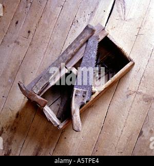 alten Werkzeugkasten mit einer Säge auf Holzboden - Stockfoto