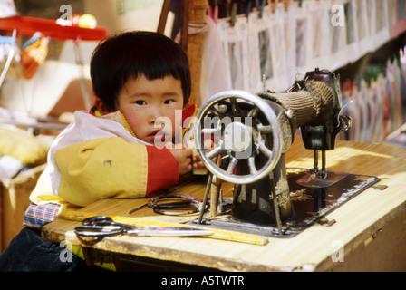 Lokale junge neben alte Nähmaschine auf Tisch am Straßenrand, Kunming, Provinz Yunnan, China. - Stockfoto