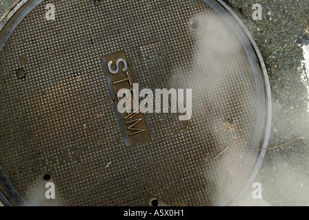 Eine Einsteigeloch-Abdeckung lässt sich Dampf in der Innenstadt von Seattle am 5. Februar 2006. - Stockfoto