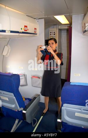 Flight Attendant zeigt, wie man einen Sicherheitsgurt zu verwenden. - Stockfoto