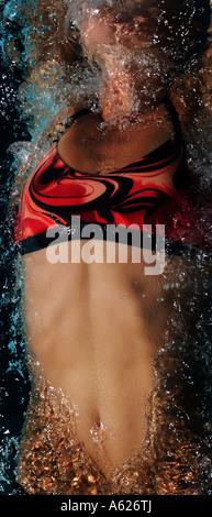 Eine junge Frau den Magen wird gesehen, wie sie auf dem Rücken in einem Pool schwimmt. - Stockfoto