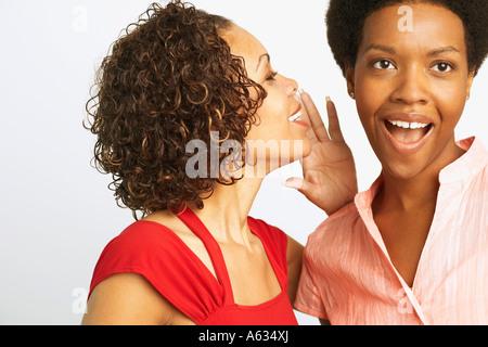 Nahaufnahme einer reifen Frau, Flüstern zu einer jungen Frau - Stockfoto