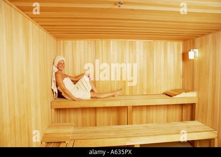 Seitenansicht einer reifen Frau in der Sauna sitzen - Stockfoto