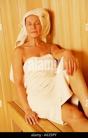 Nahaufnahme einer reifen Frau mit Handtuch in der Sauna sitzen - Stockfoto