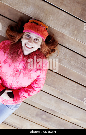 Erhöhte Ansicht einer reifen Frau liegend auf Holzstufen - Stockfoto