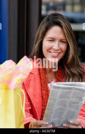 Nahaufnahme einer reifen Frau, die eine Zeitung lesen - Stockfoto