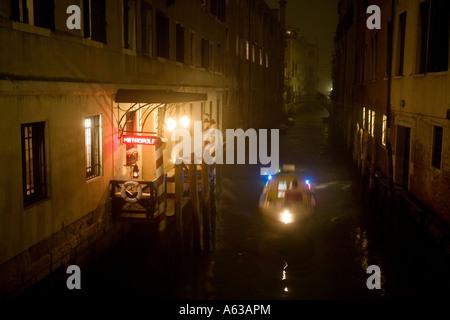 Ein Polizeiboot blau leuchtet blinkende Reisen an einem Kanal entlang vorbei an im Hotel Metropole in einer nebligen - Stockfoto