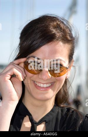 Porträt von schönen jungen türkischen Frau mit Sonnenbrille lächelnd - Stockfoto