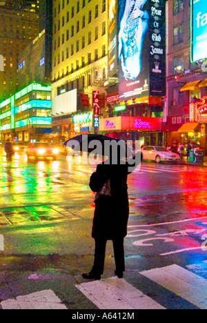 Mann hagelt Taxi mit Schirm im Regen in der Nacht, New York City Times Square, New York, USA - Stockfoto