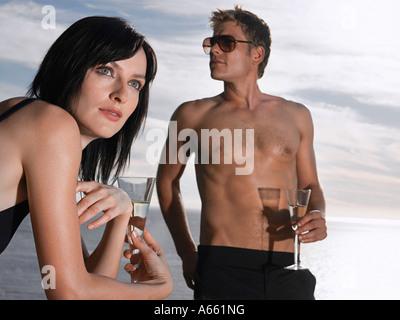 Mann und Frau trinken Champagner in der Nähe von Meer - Stockfoto