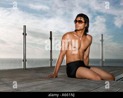 Mann im Badeanzug sitzt am Pool in der Nähe von Meer - Stockfoto