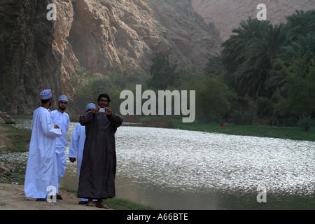 Omanische Mann Aufnahme eines Fotos des Fotografen im Wadi Shab, Oman - Stockfoto