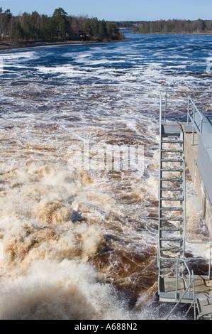 Metallischen Leitern über aufgewühlten Wasser das Wasserkraftwerk des Dammes entlädt - Stockfoto