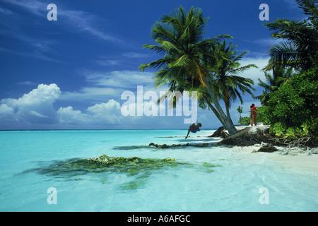 Frau in Gange unter Palme und paar umarmt auf Maayafushi Insel auf den Malediven inmitten indischen Ozean in Nord - Stockfoto