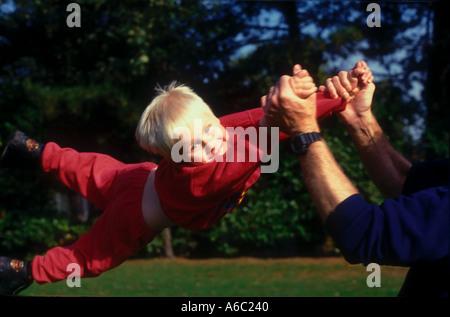 Junge wirbelte herum in der Luft durch die Arme von Vater im Park. - Stockfoto