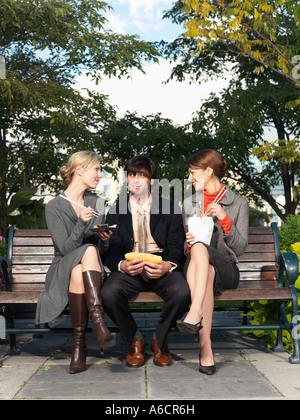 Menschen Essen auf Parkbank - Stockfoto