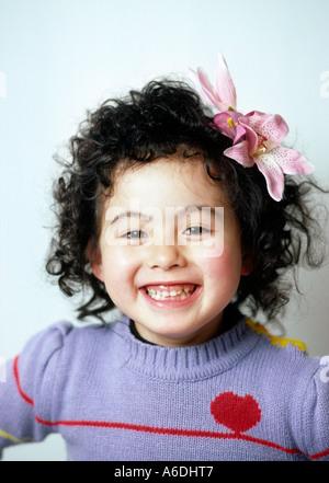 5973 fünf Jahre altes Mädchen glücklich mit Blume im Haar - Stockfoto