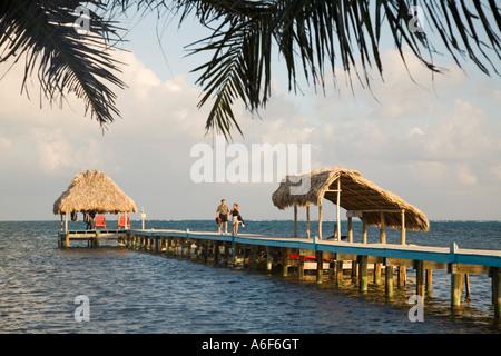 BELIZE Ambergris Caye paar Spaziergang hinunter in Richtung Restaurant Pier strohgedeckten Dächern auf Dock-Strukturen, - Stockfoto