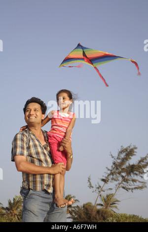 South Asian indischen Vater Holding Tochter fliegenden Drachen am Meeresstrand Shiroda Dist Sindhudurga Maharashtra, - Stockfoto