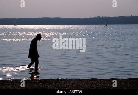 Ein einsamer alter Mann genießt einen Spaziergang in das Seewasser Seite in Bayern - Stockfoto