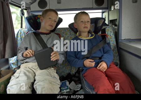 Zwei müde sechs und acht Jahre alten Jungen auf dem Rücken eines VW camping Autos - Stockfoto
