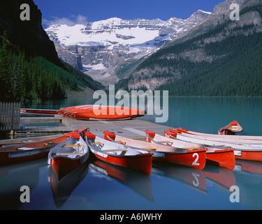 Banff Nationalpark Kanada: Rote Kanus am Lake Louise mit Mount Victoria und Victoria-Gletscher in der Ferne - Stockfoto
