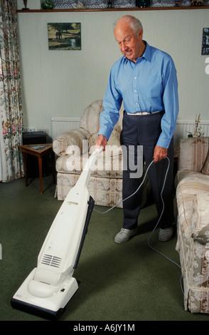 älterer Mann Lounge Teppich saugen - Stockfoto