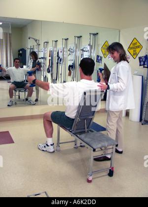 Mann im Spiegel während Krafttraining in einer Physiotherapie-Klinik mit einem Therapeuten suchen auf suchen - Stockfoto