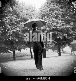Mann mit Regenschirm und Aktenkoffer im Regen - Stockfoto