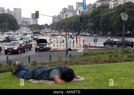 Obdachloser schläft auf einem Grünstreifen in der Mitte der Avenida 9 de Julio (B) - Stockfoto