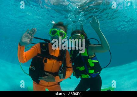 Kursleiter und Anfänger unter Wasser beim Tauchen Pool training - Stockfoto