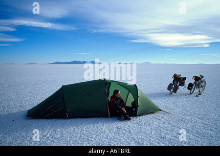 Frau allein im Zelt mit Weite des Salar de Uyuni Salz flach herum auf 3800 Metern Höhe in Bolivien mit zwei - Stockfoto