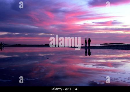 Ein paar mit einem nach Sonnenuntergang Spaziergang am Strand mit Reflexionen und einem schönen farbigen Himmel - Stockfoto