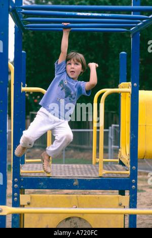 Junges Mädchen spielen im freien Schwingen speziell auf Klettergerüst - Stockfoto
